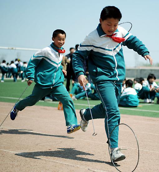 4月2日,学生们在进行推铁环比赛。   当日,济南市董家镇小学举办迎奥运追忆儿时温馨记忆,呼吁传统文化回归为主题的校园活动。活动内容丰富,形式多样,有推铁环、盘磨、踫拐、拾牌、跳方、翻花线等民间传统游戏。   新华社记者范长国摄