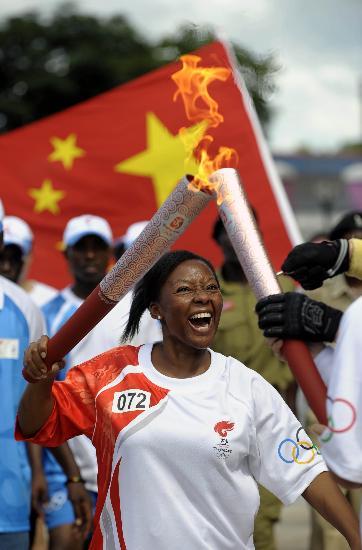 图文-奥运火炬在达累斯萨拉姆传递 两位火炬手交接