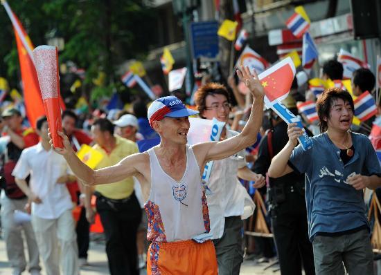 图文-北京奥运圣火在曼谷传递 老人模仿火炬手传递