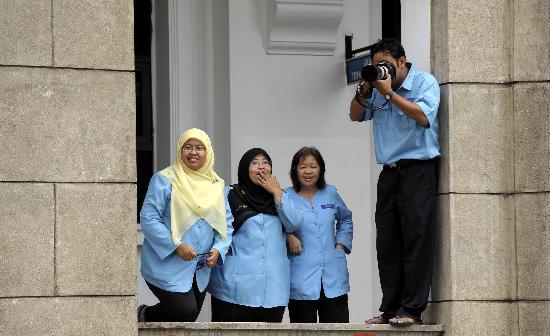 图文-奥运圣火在吉隆坡传递 一个好汉就得有三个帮