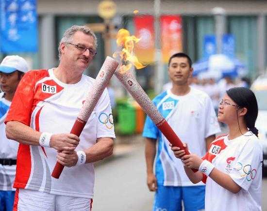图文-奥运圣火在云南昆明传递 火炬手进行交接