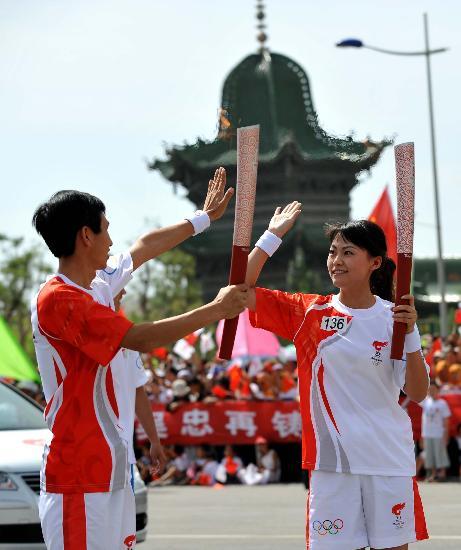 图文-奥运圣火在吴忠传递 火炬手江萍与马磊交接