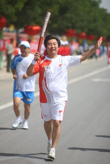 图文-奥运圣火在吴忠传递 微笑招手展露心中自豪