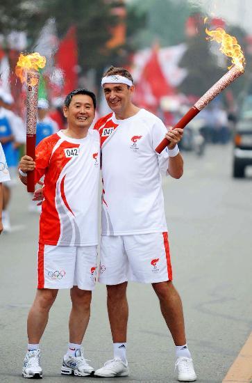 图文-奥运圣火在松原市传递 禾珂瑞与张云福交接