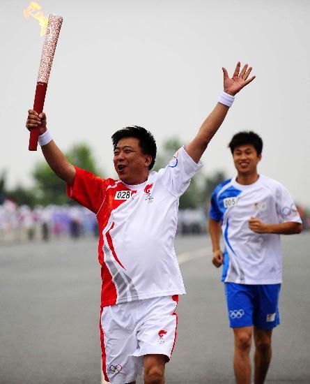 图文-北京奥运圣火在大连传递 火炬手顾善家招手