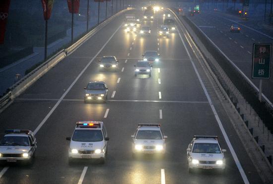 图文-57辆高清电视转播车到达北京 警车保驾护航