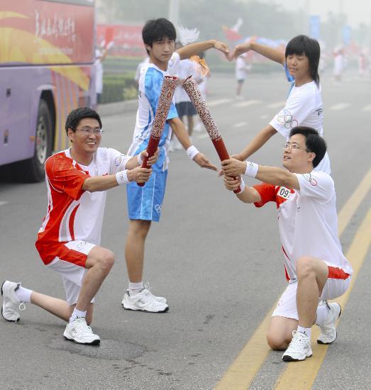 图文-北京奥运圣火在安阳传递 邢建国与康进忠交接