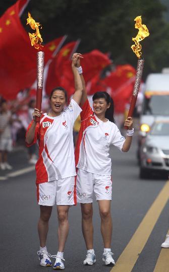 图文-奥运圣火在乐山传递 牵手祝贺火炬胜利交接