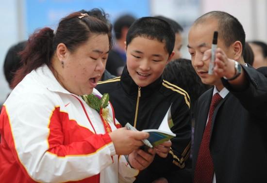 图文-奥运冠军助威倡导全民健身唐功红给小朋友签名